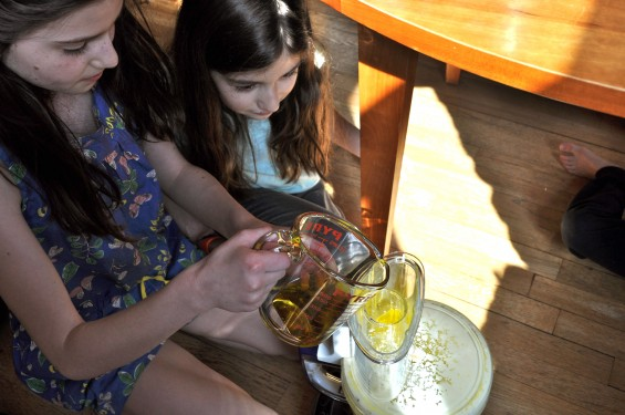 pouring in the oil to make homemade mayonnaise